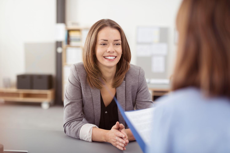 Eine junge Frau lächelt beim Vorstellungsgespräch