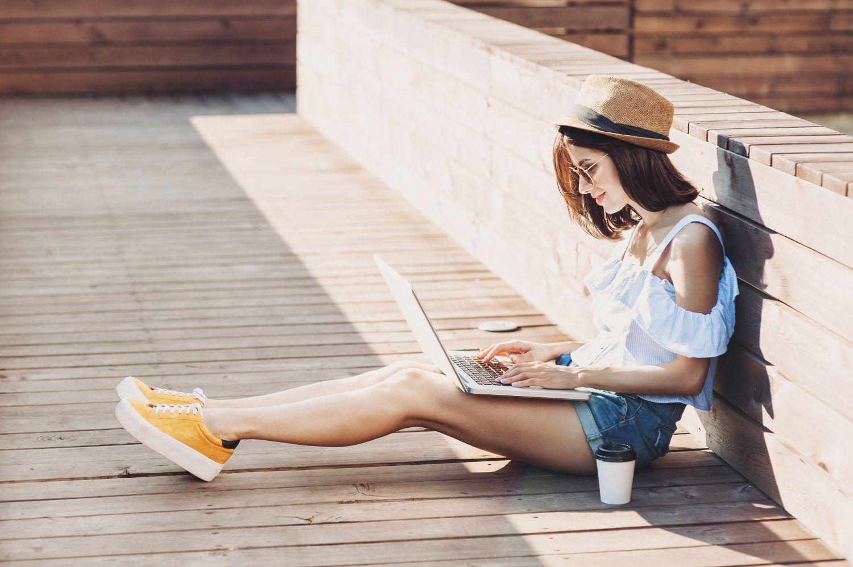 Eine Frau arbeitet im Freien an ihrem Laptop