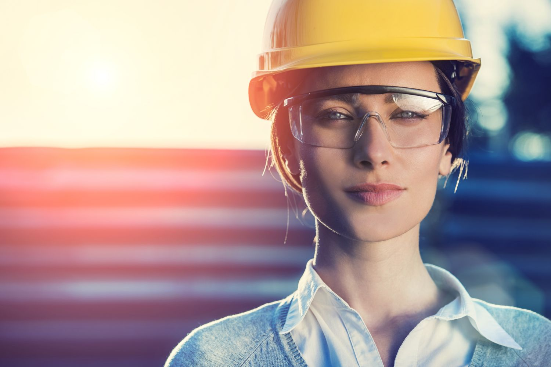 Eine Frau mit einem Bauhelm und Schutzbrille auf der Baustelle