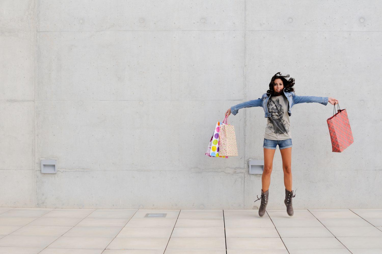 Frau springt mit Einkaufstüten in den Händen in die Luft