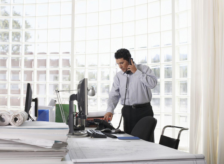 Mann telefoniert an seinem Arbeitsplatz