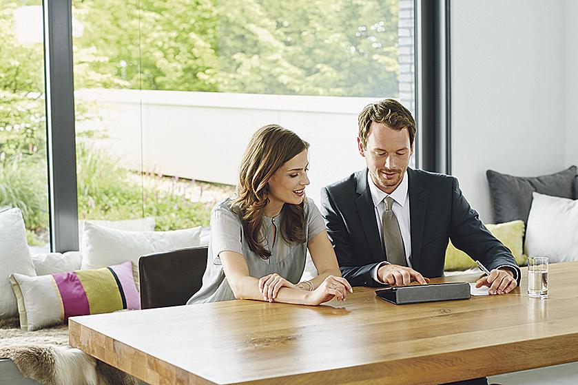 Berater sitzt mit Kundin vor Tablet-Computer am Tisch