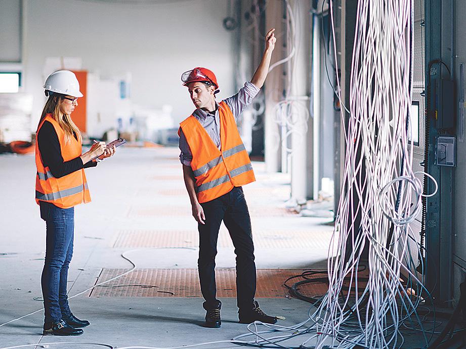 Zwei Bauarbeiter tauschen sich auf einer Baustelle aus. Thema: Jobs in der Bauwirtschaft