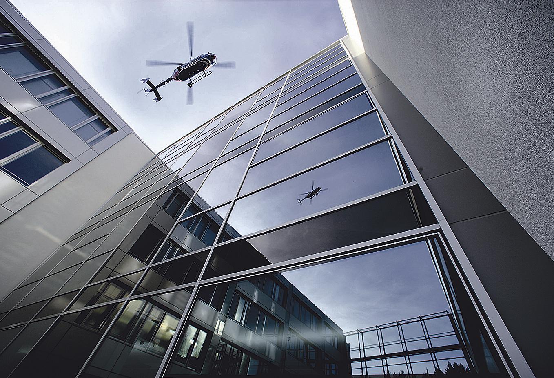Hubschrauber spiegelt sich in verglaster Häuserfront. Thema: Systems Engineering im Luftfahrt-Umfeld