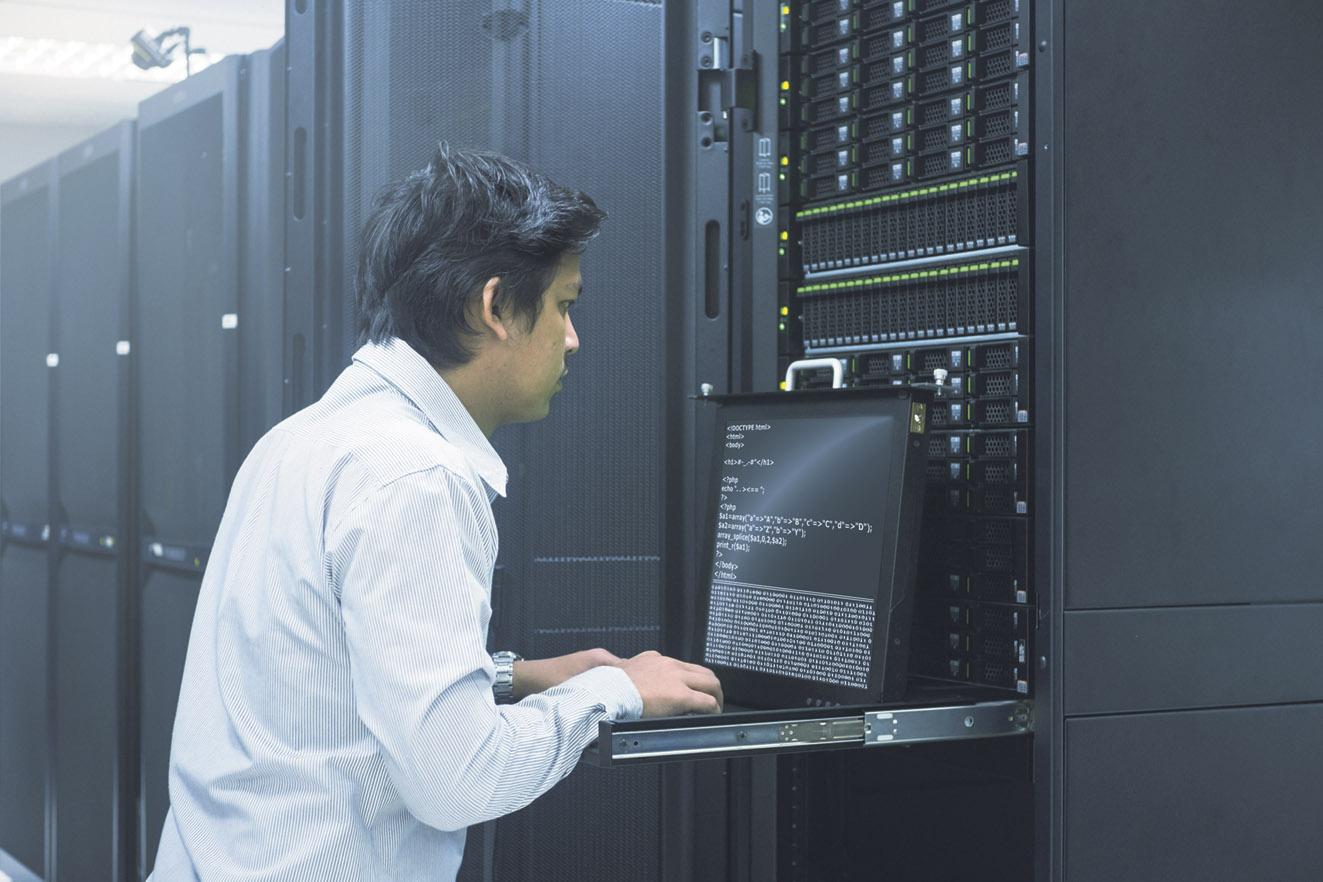 Ein Mann steht in einem Serverraum und tippt etwas in ein Laptop. Thema: Karriere in der IT