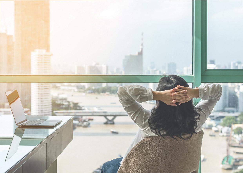 Eine Frau sitzt entspannt im Büro und schaut aus dem Fenster.