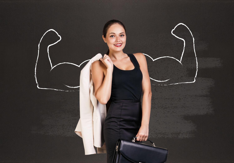 Frau mit Anzugjacke über der Schulter und Aktentasche steht vor einer Tafel, auf der Arme mit Siegerpose aufgemalt sind.