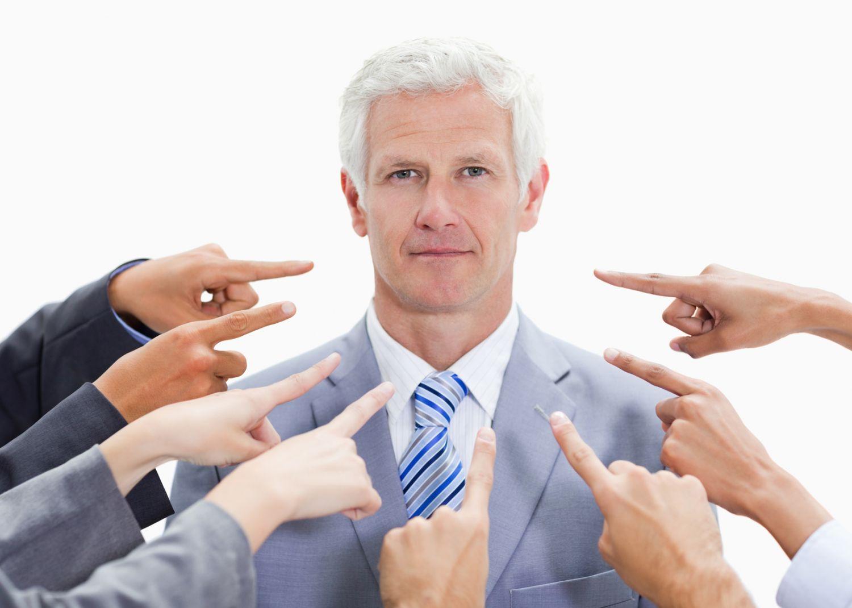 Viele Menschen deuten mit Fingern auf einen Mann. Thema: Kritik am Vorgesetzten