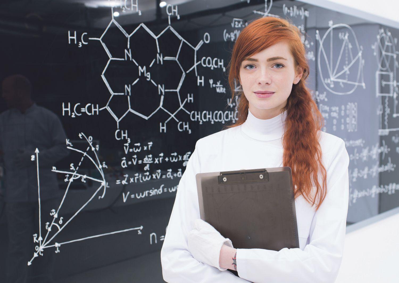 Eine Frau vor einer Tafel mit chemischen Formeln. Thema: Frauen in technischen Berufen