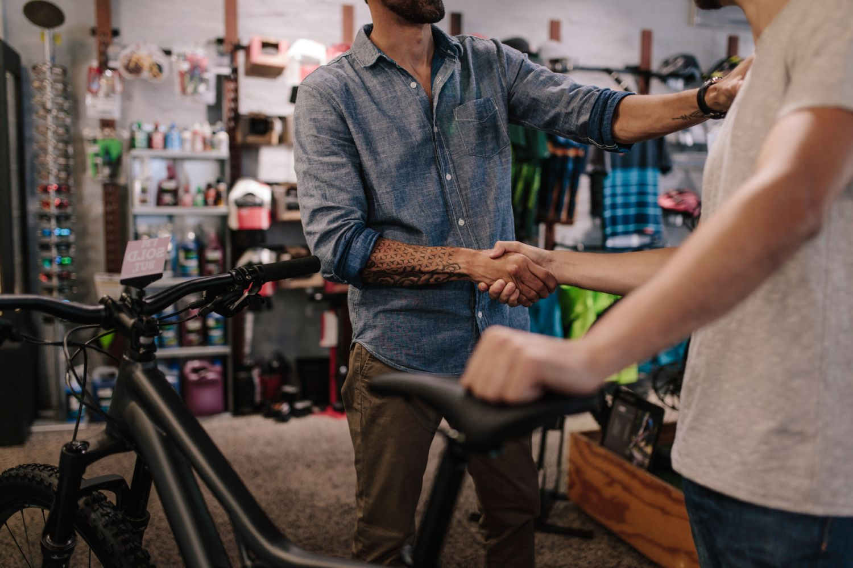 Ein Kunde und ein Fahrradmechaniker schütteln einander die Hand. Quelle: iStock/jacoblund