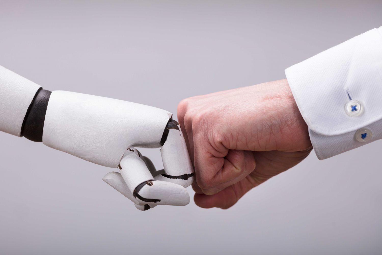 Roboter-Faust und menschliche Faust treffen aneinander zum Gruß.