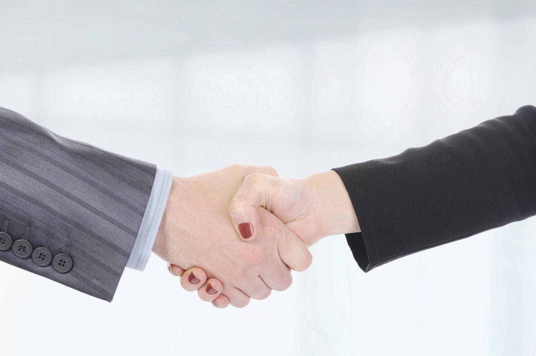 Eine Frau und ein Mann reichen sich die Hand. Thema: Karriere unter Männern