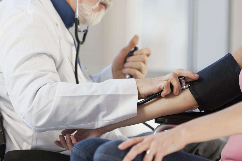 Ein Arzt misst den Puls eines Patienten. Thema Jobs im Gesundheitswesen