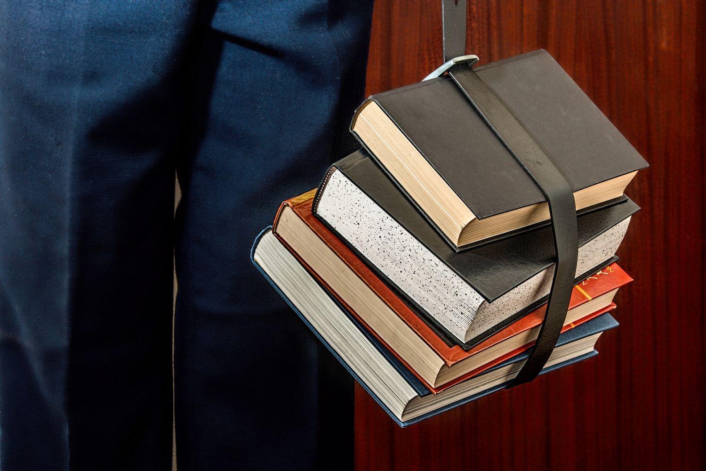 Ein Schüler trägt mit einem Ledergurt geschnürte Schulbücher. Thema: Berufswahl von Jugendlichen