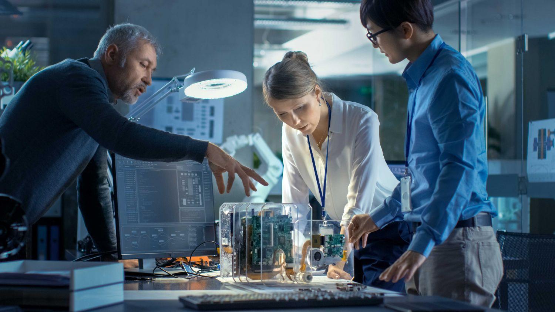 Ingenieure betrachten Modell einer Maschine am Schreibtisch