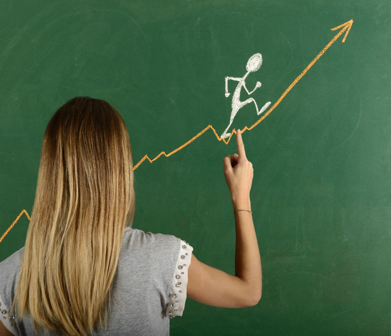 Eine Frau zeichnet ein Strichmännchen an eine Tafel. Thema: Frauen im Beruf
