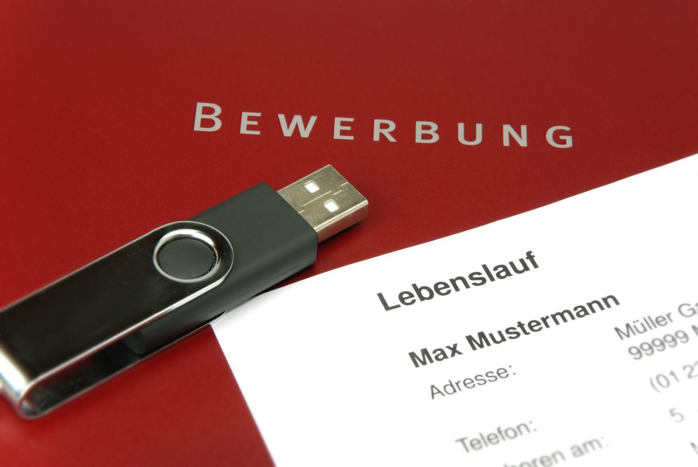 Auf einer Bewerbungsmappe liegen ein USB-Stick und ein Lebenslauf. Thema: die richtige Bewerbung