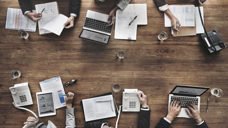 Was ist New Work? Menschen an einem Konferenztisch in der Aufsicht.
