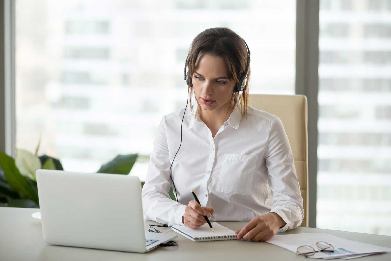 Frau lernt am Computer und macht sich nebenbei Notizen. Thema: Online-Kurse