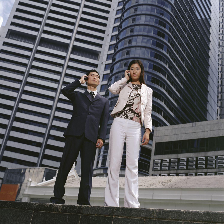 Eine Frau und ein Mann telefonieren vor einer Hochhauskulisse. Thema Arbeitsmarkt in Deutschland