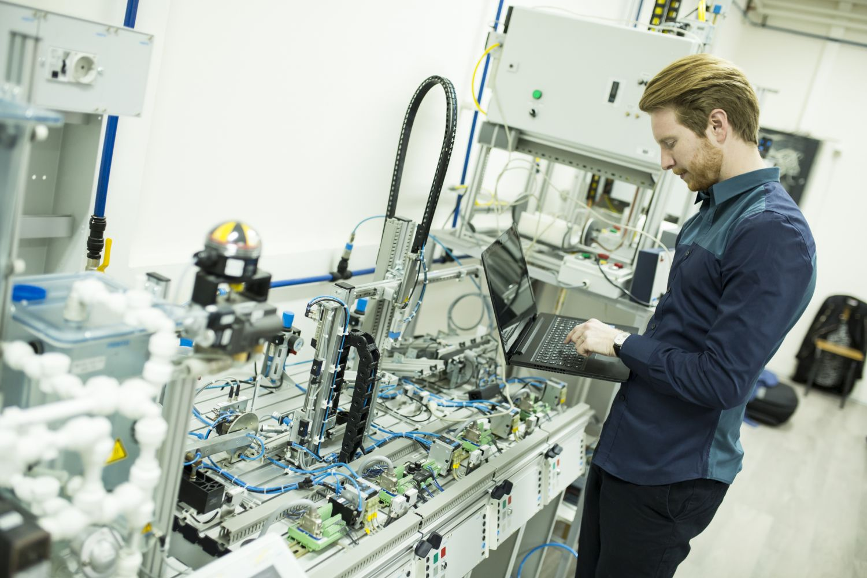 Ein Mann steht mit einem Laptop in einem Labor. Thema: Ingenieursberufe