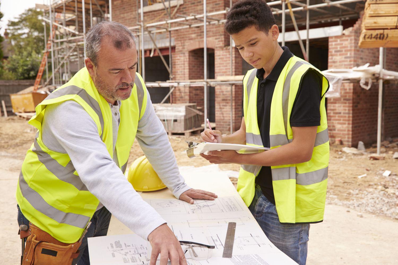 Zwei Bauarbeiter besprechen auf einer Baustelle einen Plan. Thema: die richtige Ausbildung