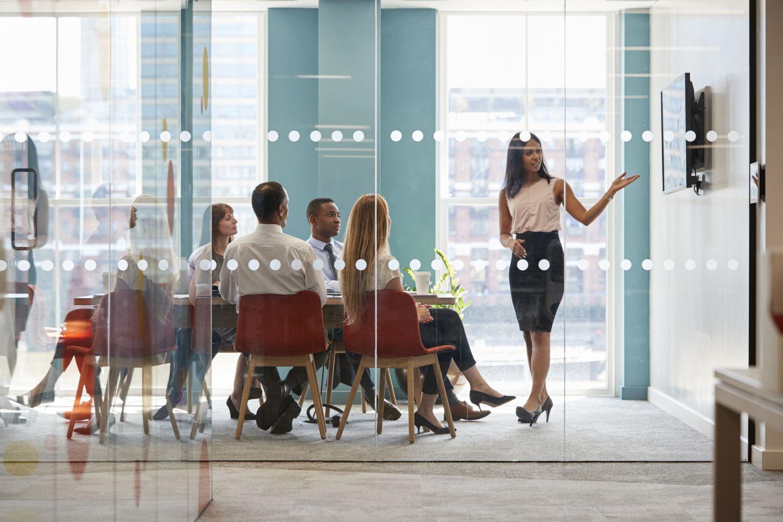 Eine Unternehmerin präsentiert Mitarbeitern etwas in einem Konferenzraum. Thema Führungskräfte