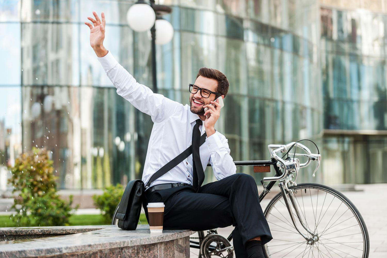 Ein Mann winkt beim telefonieren. Frage: Wie viel verdienen die Deutschen?