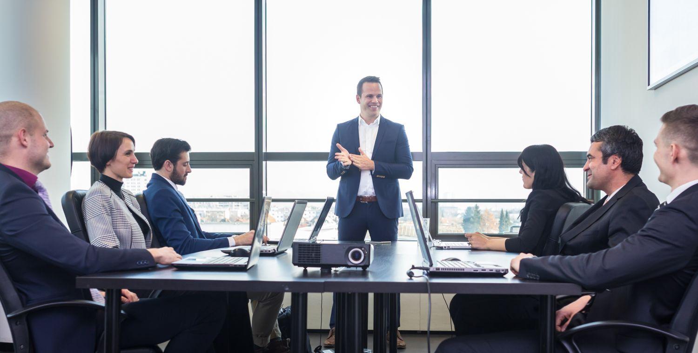 Führungskraft hält Präsentation vor Mitarbeitern, die um einen Tisch sitzen.
