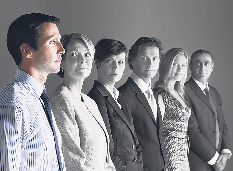Geschäftsleute stehen in einer Reihe und blicken auf ihre Führungskraft.