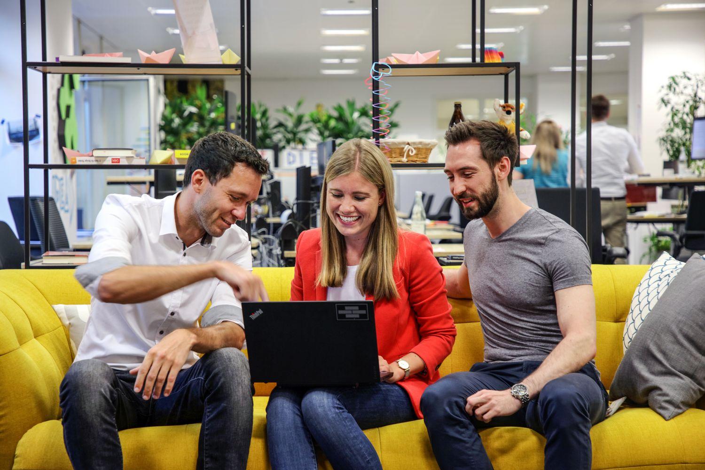 Dreiergruppe arbeitet auf dem Sofa an einem Laptop.
