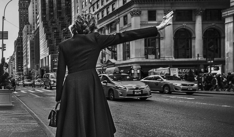 Eine Frau ruft auf der Straße ein Taxi. Thema: Frauen im Job