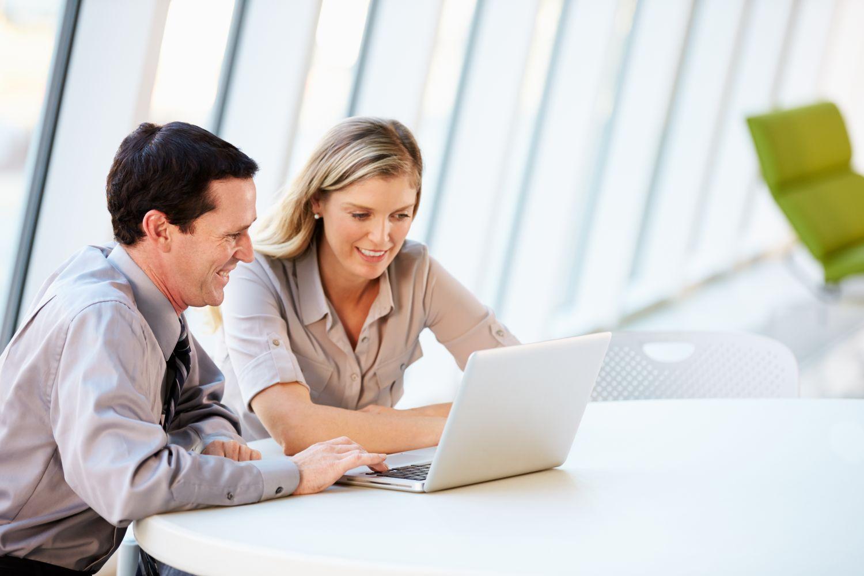 Eine Frau und ein Mann betrachten an einem Konferenztisch ein Dokument. Thema: Gleichberechtigung im Job