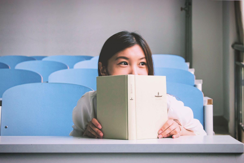 Eine Frau hält ein Buch vor ihr Gesicht. Thema: Frauen und Weiterbildung