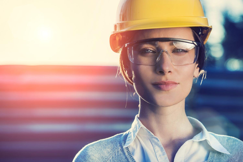 Eine Frau mit einem Bauhelm und Schutzbrille auf der Baustelle. Thema: Studium oder Ausbildung?