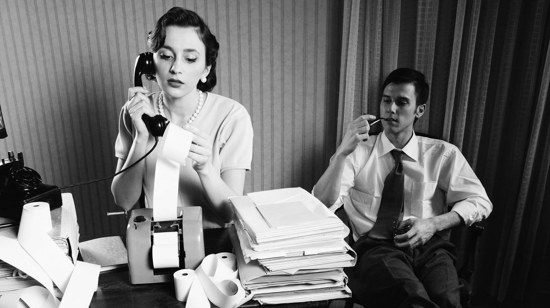 Eine Frau telefoniert, im Hintergrund sitzt ein Mann. Thema: Gehalt von Männern und Frauen im Vergleich