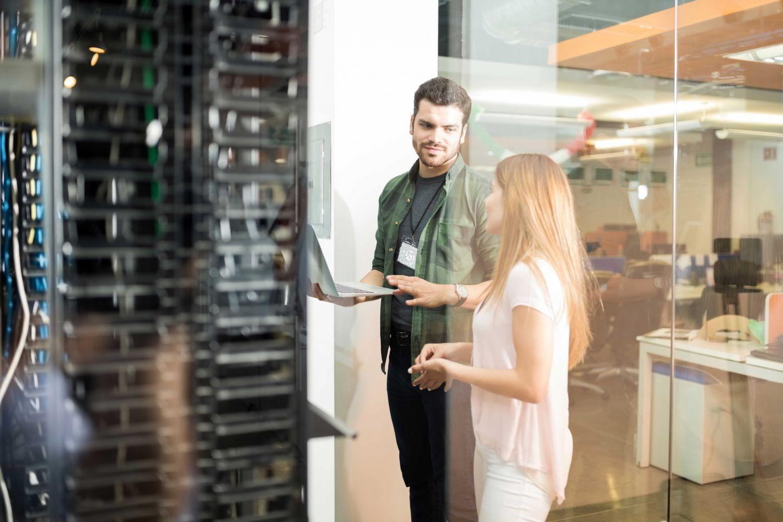 IT-Spezialist erklärt einer Kollegin etwas. Thema: IT-Management