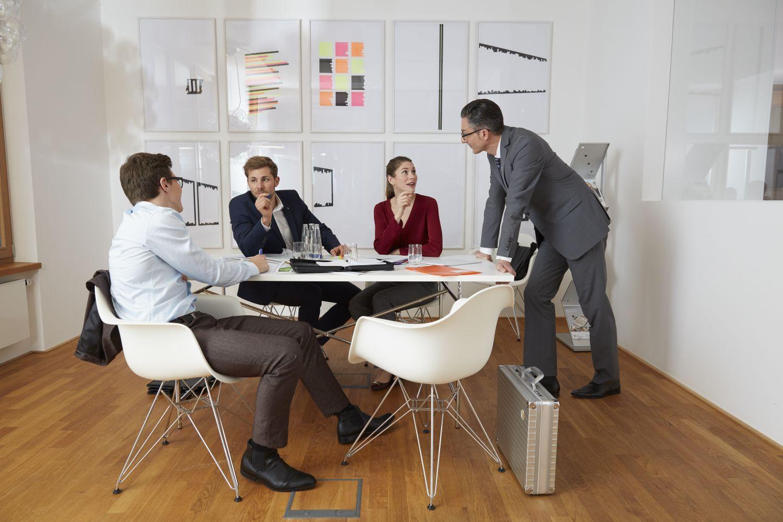 Berater und Kunden sitzen um einen runden Tisch herum.