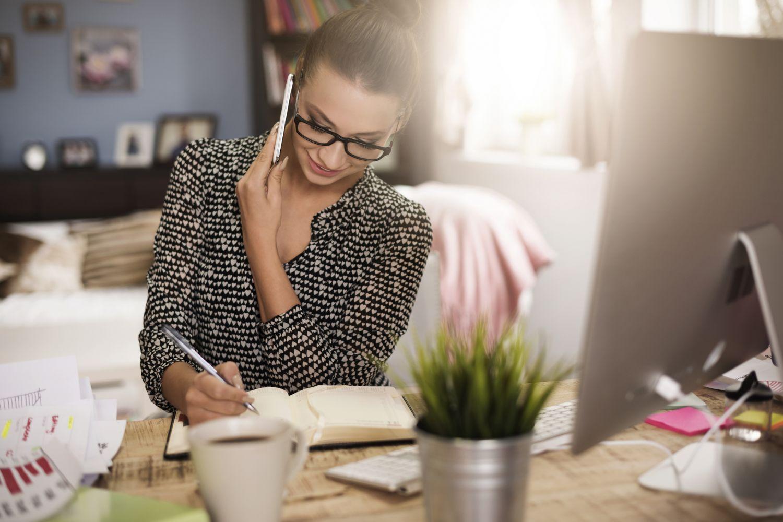 Eine Frau schreibt beim Telefonieren in ein Notizbuch. Thema Benefits 2016